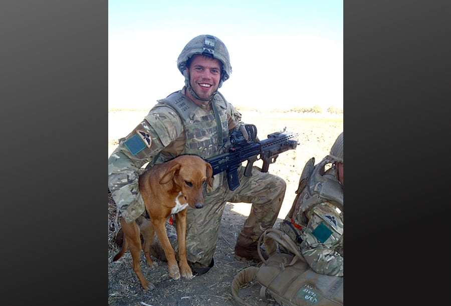 Paratrooper Conrad Lewis hugging his adopted dog peg on patrol in Afghanistan